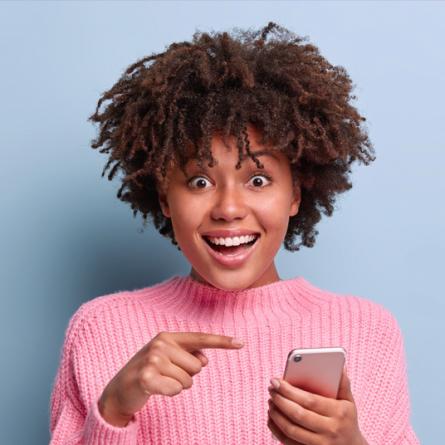 mulher negra com blusa rosa apontando para o celular que está segurando com a mão esquerda e sorrindo