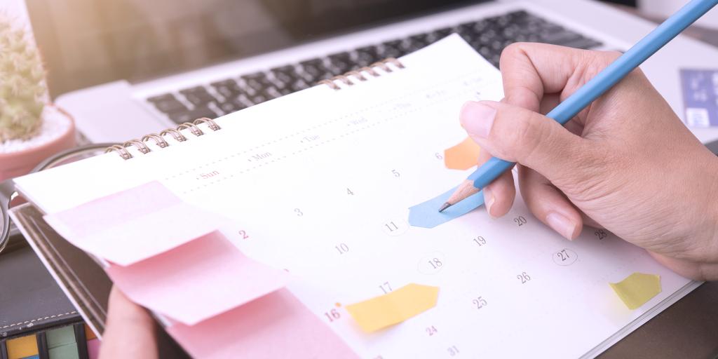 pessoa fazendo anotações em seu planner e calendário