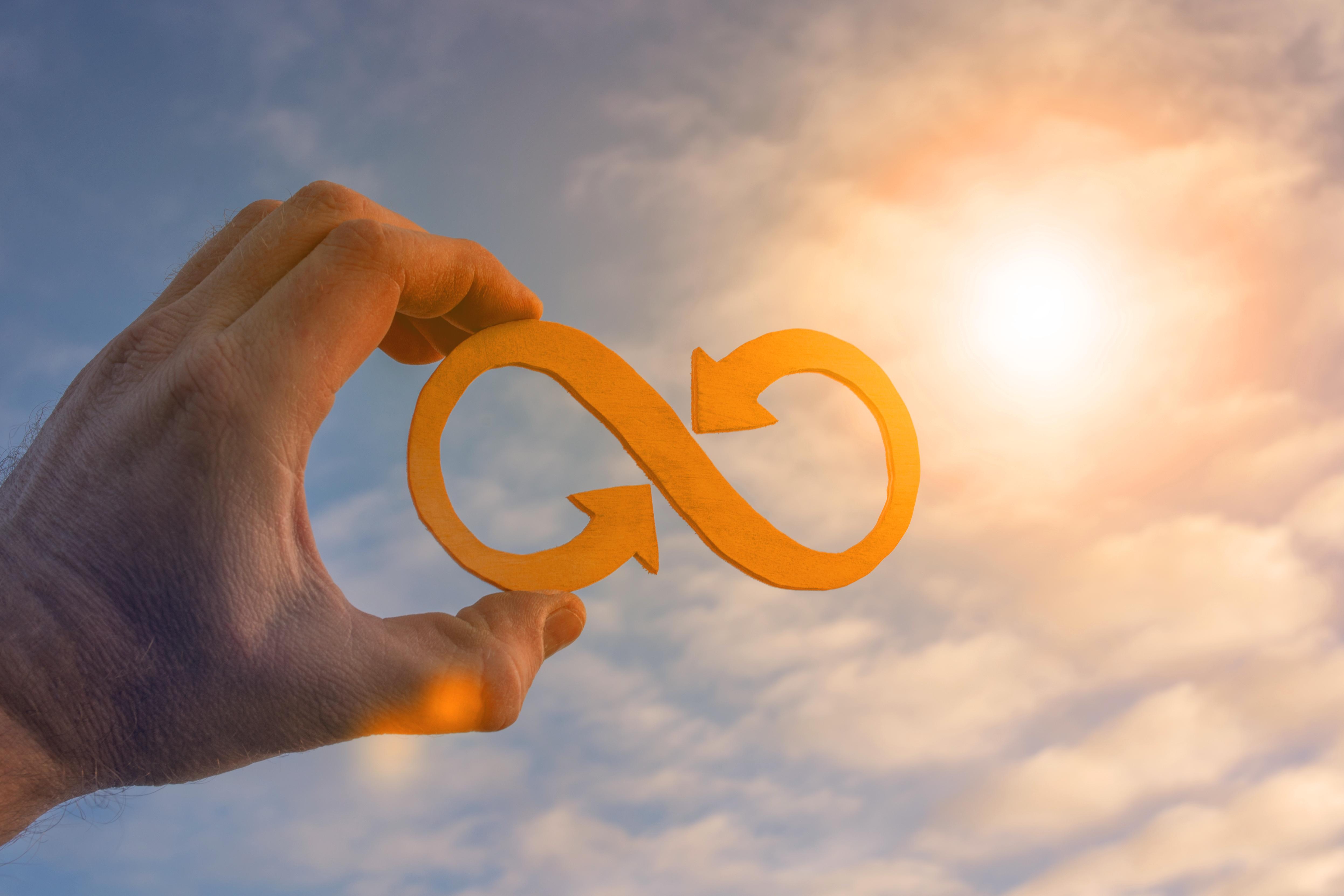 mão segurando o símbolo economia circular